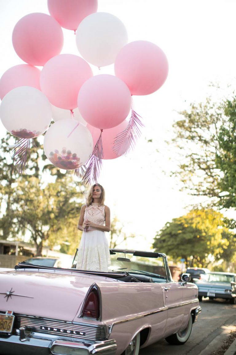 Women Standing in A Car with Balloons